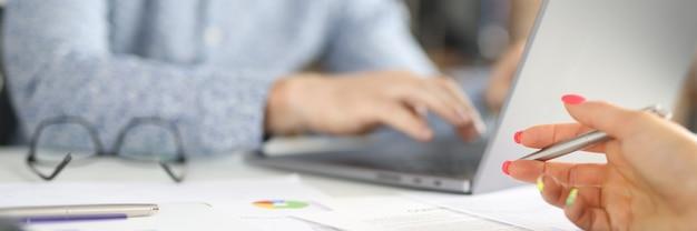 На рабочем месте в офисе мужчина сидит за ноутбуком, женская рука держит ручку над коммерческими графиками