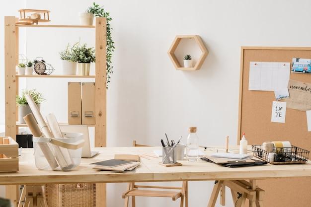 Рабочее место в студии у белой стены с свернутыми бумагами в пластиковом контейнере, тетрадями, бутылкой воды и другими вещами на деревянном столе