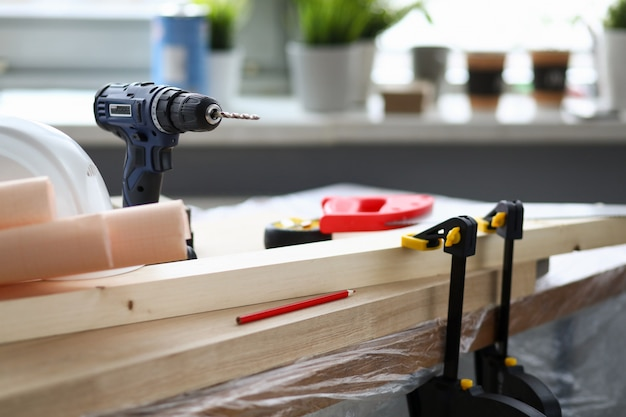 At workplace joiner is hand drill, vise holds bar