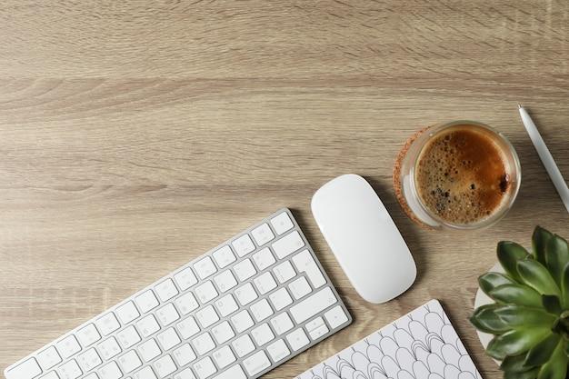 職場。キーボード、マウス、コーヒー、木製のテーブル、トップビューで植物