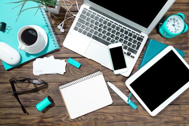 직장, 노트북, 태블릿 pc 및 테이블 위의 전화