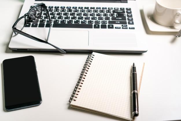 Рабочее место, портативный компьютер, тетрадь и мобильный телефон на белой таблице концепция работы дела.