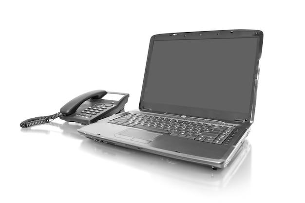 Ноутбук на рабочем месте с телефоном, изолированным на белом