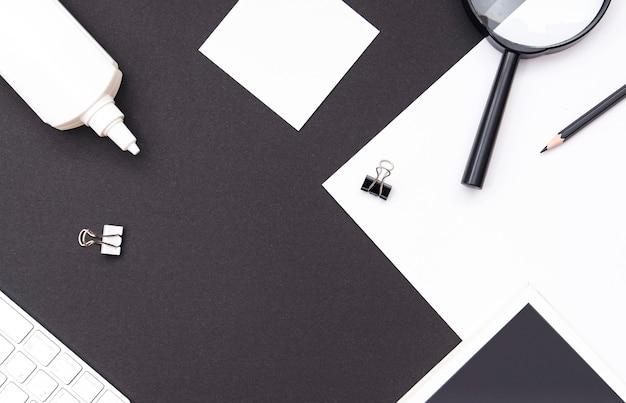 대조적인 흑백 톤의 직장 모형. 편지지, 책, 빈 시트, 돋보기, 키보드 및 연필이 있는 사무실 책상. 상위 뷰, 텍스트를 위한 공간