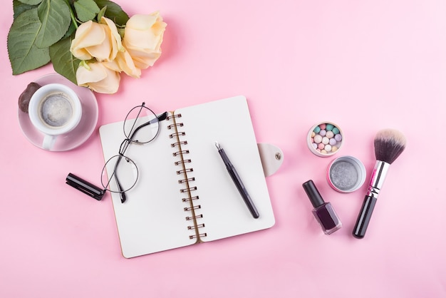 Workplace mockup with notebook, glasses, roses and accessories
