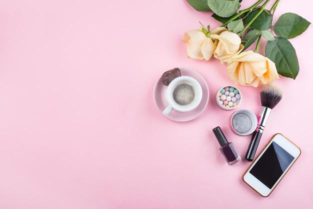 Макет на рабочем месте с розами, телефон и аксессуары на розовом фоне