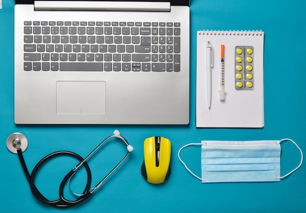 Workplace of a modern doctor. laptop, wireless mouse, notebook, stethoscope, pills on a blue background. top view, minimalist trend