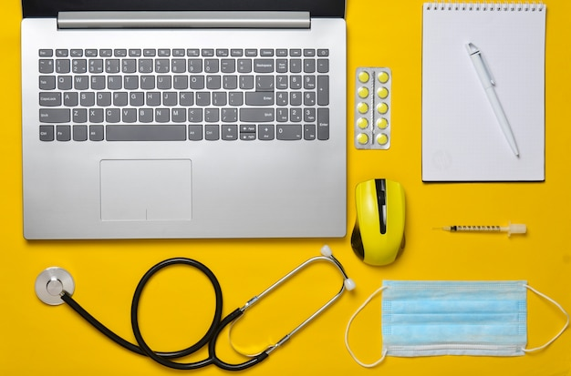Workplace of a modern doctor. laptop, wireless mouse, notebook, stethoscope, pills on a yellow pastel background. top view, minimalist trend