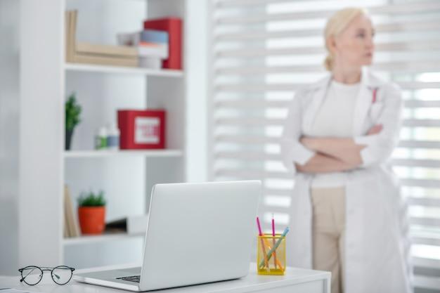 医者の職場。窓際に立っている女医の職場にメガネとノートパソコン。