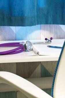 На рабочем месте врача в бело-голубых тонах стоит стетофонендоскоп тетрадь