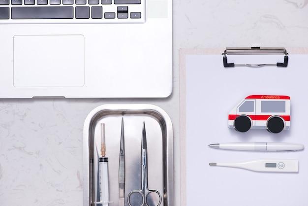 Рабочее место врача. ноутбук, буфер обмена и другие вещи на столе.