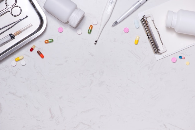 Рабочее место врача. стетоскоп, буфер обмена, таблетки и другие вещи на столе.
