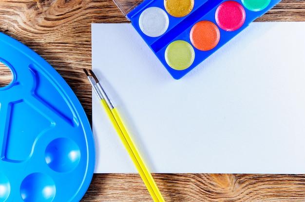 アーティストの職場、上面図、コピースペース。白い机の上にブラシで絵の具と木製の画家の男