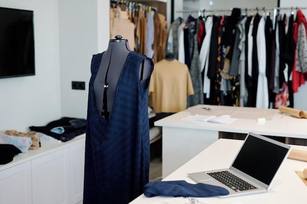 現代の女性の裁縫師または仕立て屋の職場、マネキン、ラップトップ、机の上の布地に未完成の衣料品