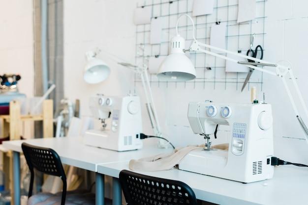 Рабочее место современной швеи со стулом, письменным столом, лампой и электрической швейной машиной в цехе фабрики