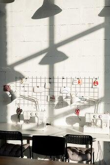 ランプ、ミシン、椅子、便箋、小さな写真が付いた長いテーブルを備えた現代的な仕立て屋や針子の職場