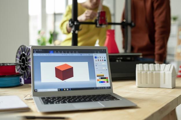 ノートパソコンと新しい3dモデルの写真を展示しているクリエイティブエンジニアまたはデザイナーの職場