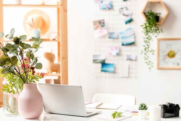 ラップトップ、事務用品、机の上に花の組成物を持つインテリアデザイナーの職場