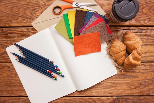 Рабочее место модельера. карандаши, кофе и вид сверху ткани. творческий фон, художественная школа, швейное вдохновение и концепция идеи