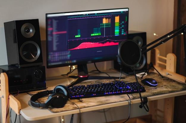 Рабочее место музыканта за домашним столом с микрофоном компьютера и наушниками, звуком рабочего процесса компьютера