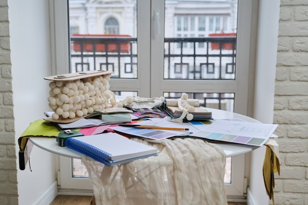 Рабочее место текстильного дизайнера, на столе поддоны с тканями