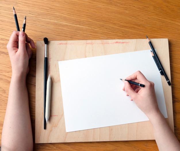 Рабочее место художника с художественными материалами. художник рисует карандашом