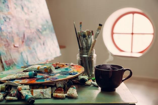 Рабочее место художника с кистями, красками, холст на мольберте и кружка с горячим напитком