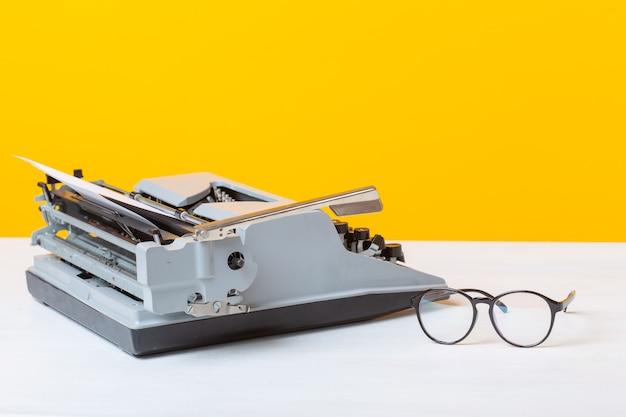 黄色い壁のテーブルの上に秘書兼ビジネスタイプライターのマネージャーとメガネの職場があります。オフィスワークのコンセプト。