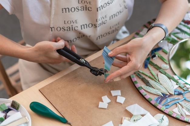 Рабочее место мастера женской мозаики держит в руках инструмент для мозаичных деталей в процессе изготовления ...