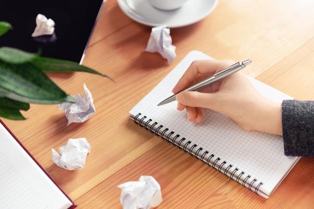 作家、リライターの職場。ペンを持ってメモ帳で書く女性の手。