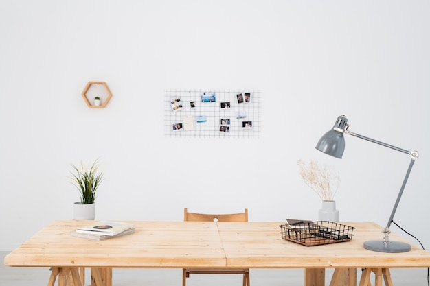 Workplace of office manager or freelancer with lamp, plants in pots and other supplies on wooden table against white wall