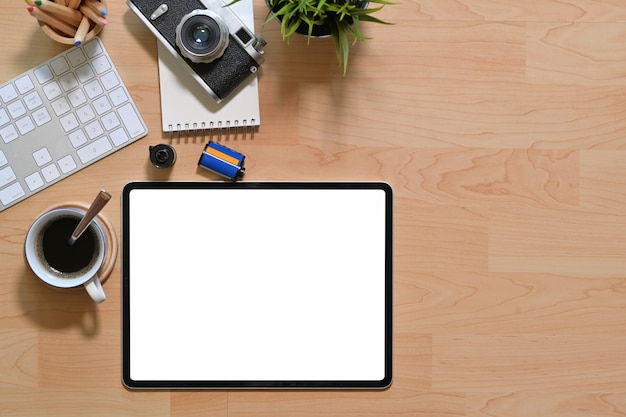 Workplace office wooden desk with blank screen tablet, camera, films and office supplies