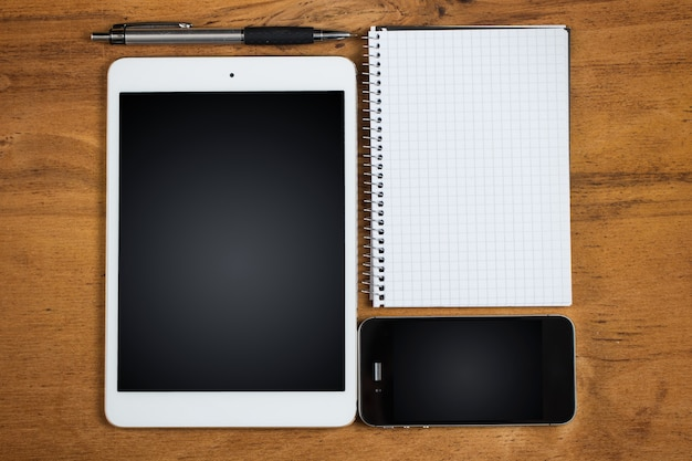 Рабочее место. телефон, планшет и блокнот на столе