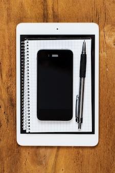 職場。テーブルの上の電話、タブレット、メモ帳