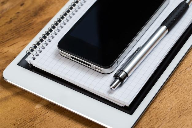 Posto di lavoro. telefono, tablet e blocco note sul tavolo