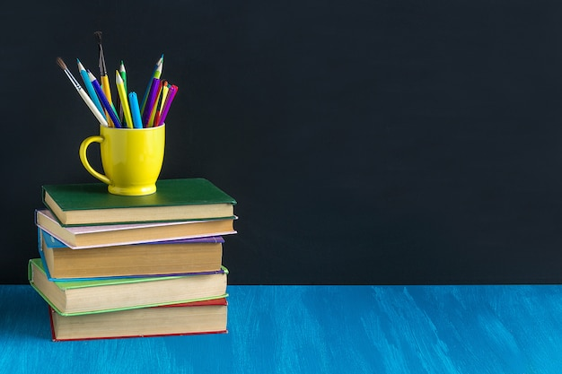 Workplace pupil books stationery on blue table on background bla