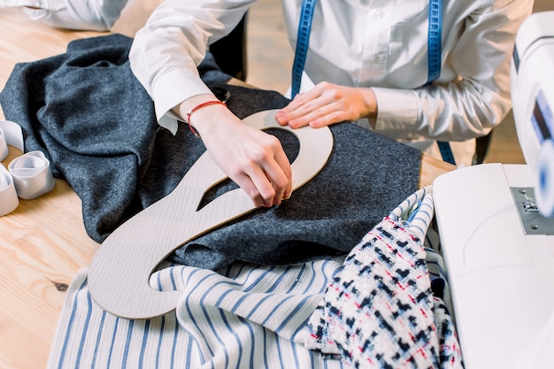 Workplace of seamstress. dressmaker cuts pants detail on the sketch lines. pattern, scissors, tape measure, and a sewing machine. dressmaker, fashion designer, tailor and people concept
