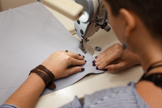На рабочем месте швея. швейная промышленность. девушка шьет на швейной машинке. заводская одежда.