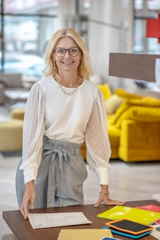 Workplace, shop interior. joyful elegant woman in glasses standing near her desk, resting her hands on it, in excellent mood.