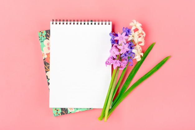 Workplace with bouquet of hyacinths flowers, white notepad on pink background flat lay top view mock up