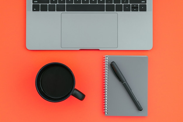 Workplace with a colored surface. laptop, a cup of coffee, a notepad with a pen isolated on a red background
