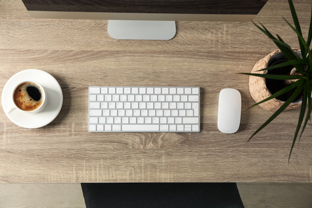 Workplace with computer, cup of coffee and plant on wooden table, top view