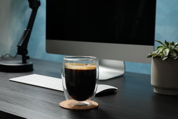 コンピューター、コーヒーのガラス、黒い木のテーブルに植物のある職場をクローズアップ