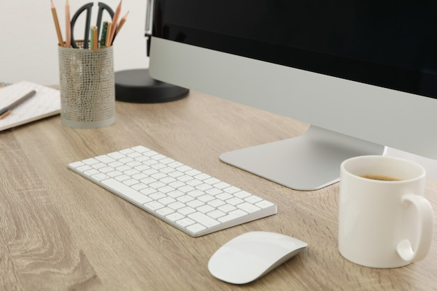 コンピューター、キーボード、木製のテーブルにコーヒーのカップを持つ職場をクローズアップ