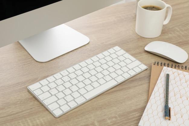 コンピューター、キーボード、木製のテーブルの上のノートブックと職場をクローズアップ