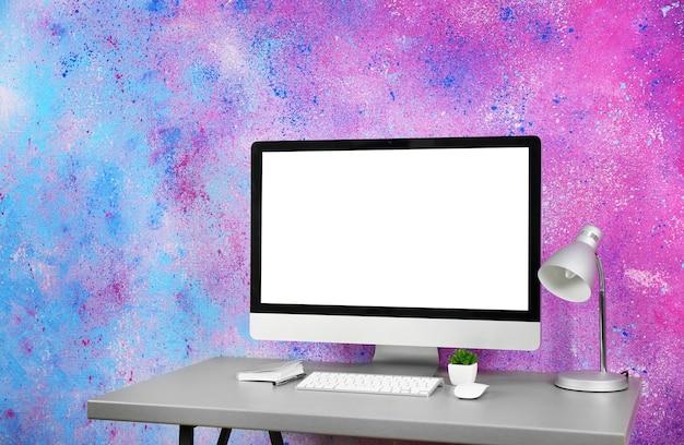 現代の部屋のテーブルにコンピューターを置いた職場