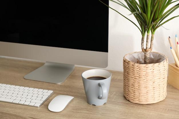 コンピューター、植物、木製のテーブルの上にコーヒーを1杯と職場をクローズアップ