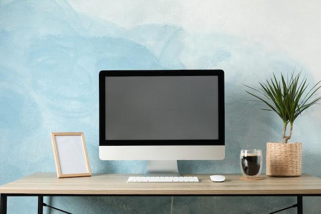 コンピューター、植物、木製のテーブルの上にコーヒーを1杯と職場。明るい青の背景