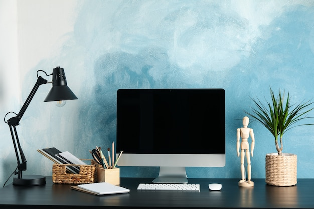 Workplace with computer and plant on wooden table. blue and white