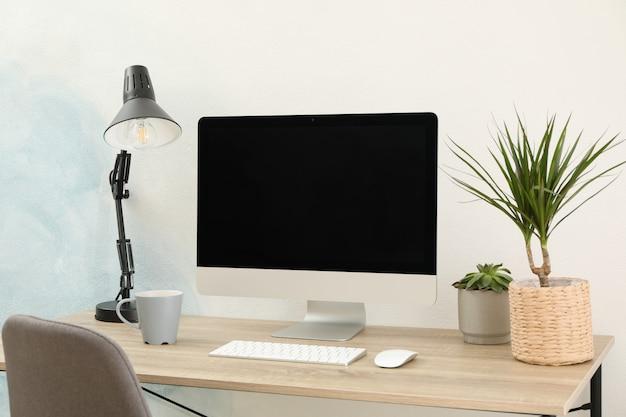 コンピューター、植物、木製のテーブルの上にランプのある職場。空の黒い画面